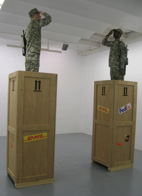 Kaksi korkeaa puista laatikkoa, joiden molempien päällä seisovat sotilaat toisiaan katsoen.