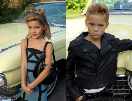 Kaksi kuvaa vierekkäin. Toisessa auton edessä seisoo lapsi jolla on pitkät hiukset, mekko, käsilaukku ja meikkiä. Toisessa kuvassa auton edessä seisoo lapsi jolla on lyhyet hiukset ja musta nahkatakki.