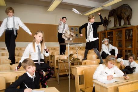 Lapsia luokkatilassa. Osa istuu, osa seisoo, osalla on lyhyet hiukset ja osalla pitkät. Kaikilla on valkoinen kauluspaita, osalla kravatti ja joillakin hame.