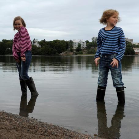 Kaksi henkilöä seisoo rantavedessä kumisaappaat jalassa. Toisella on vaaleanpunainen raitapaita, toisella sininen raitapaita.