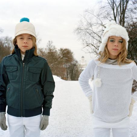 Kaksi henkilöä vierekkäin. Toisella on nahkatakki ja lippalakki, toisella valkoinen neulepusero, valkoinen pipo ja meikkiä.
