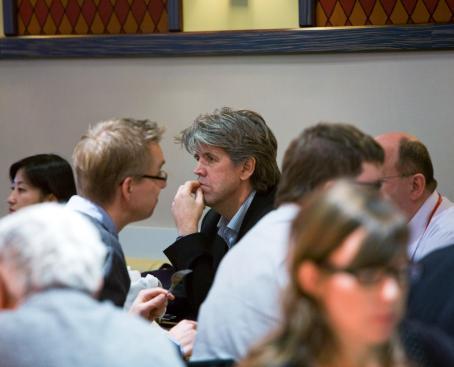 Ihmisiä ravintolassa. Kuva on tarkentunut harmaahiuksiseen mieheen, kaikki muut ovat epätarkkoja.