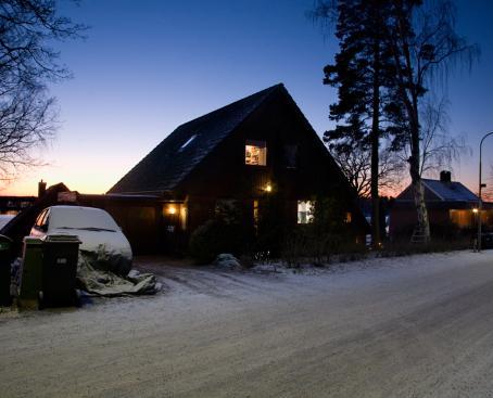 Hämärässä lumisessa maisemassa talo, jonka ikkunoista tulee valoa.