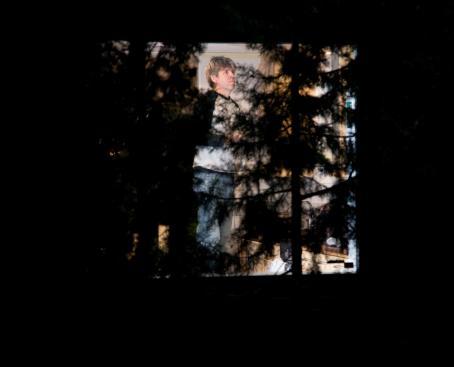 Pimeyden keskellä ja puitten takana ikkunassa mies.