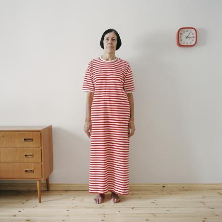 Valkoisen seinän edessä seisoo nainen, jolla on päällään punavalkoraitainen pitkä mekko. Hänellä on musta polkkatukka.