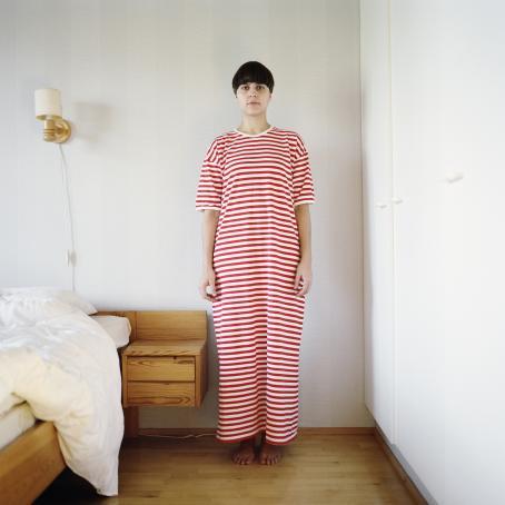 Sängyn vieressä seisoo nainen, jolla on päällään punavalkoraitainen pitkä mekko. Hänellä on lyhyet mustat hiukset.