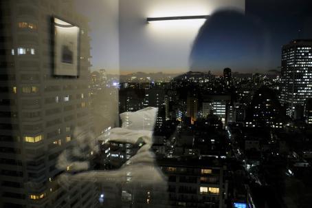 Näkymä ikkunasta, josta näkyy kaupungin rakennuksia. Ikkunasta heijastuu huoneessa oleva sänky.