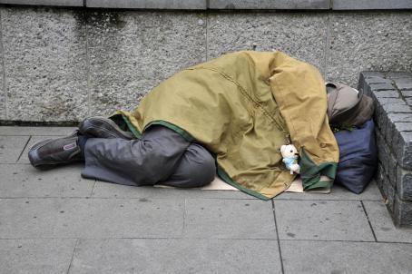 Kadulla kivisen aidan edessä makaa ihminen. Hänen päällään on takki ja huppu niin että kasvoja ei näy. Takista roikkuu pieni valkoinen pehmonalle.