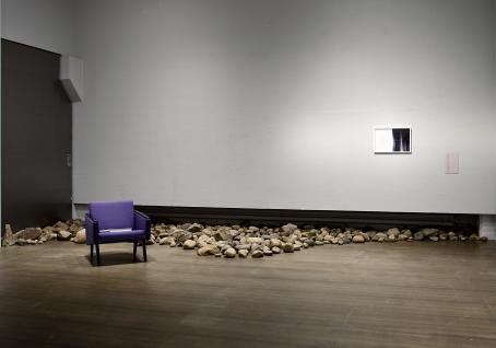 Huone, jonka seinänvierustalla on kiviä. Kivien edustalla on violetti tuoli.