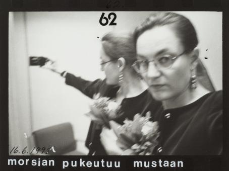 """Heilahtaneessa mustavalkoisessa kuvassa nainen pitää kädessään kameraa ja hänen takanaan näkyy sama peilikuvana. Hänellä on kädessään kukkakimppu. Kuvan yläreunassa on numero 62 ja alareunassa päivämäärä 16.6.1995 sekä teksti """"morsian pukeutuu mustaan""""."""