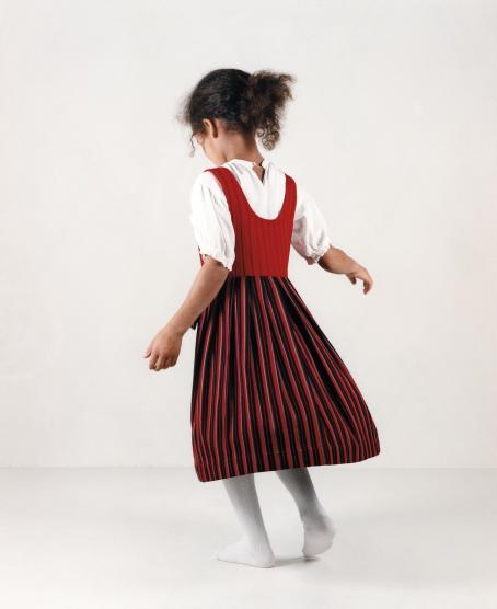 Tummaihoinen tyttö selin päällään valkoinen lyhythihainen paita, valkoiset sukkahousut ja punasävyinen liivimekko päällään.