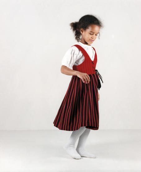 Tummaihoinen tyttö päällään valkoinen lyhythihainen paita, valkoiset sukkahousut ja punasävyinen liivimekko.