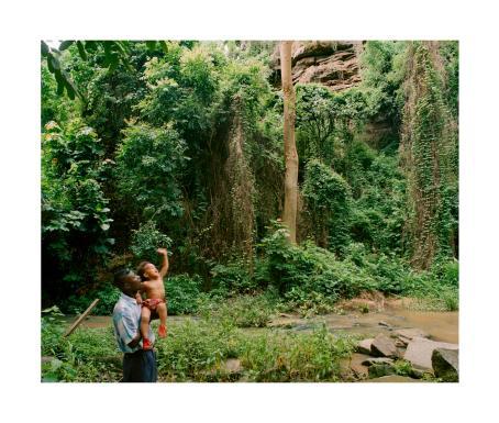 Tummaihoinen mies pitää sylissään tummaihoista lasta, joka huiskuttaa kädellään. Heidän takanaan on vihreää sademetsää ja pieni puro.