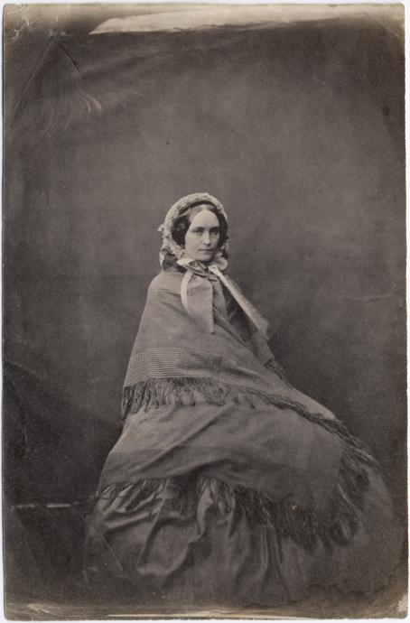 Vanhassa mustavalkoisessa kuvassa istuu nainen, jolla on iso mekko ja hartioilla huivi. Hänellä on myös päässään huppu tai huivi.