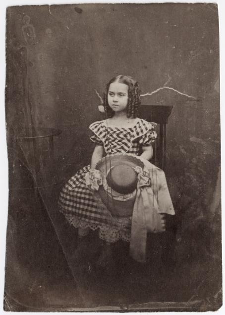 Vanhassa mustavalkoisessa kuvassa tuolilla istuu tyttö, jolla on mekko ja kiharat hiukset. Hän pitää kädessään hattua.