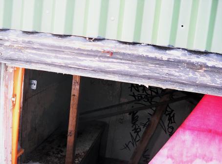 Vihreää peltiä, jonka alla jonkunlainen tila. Tilassa on graffiteja seinällä ja penkki.