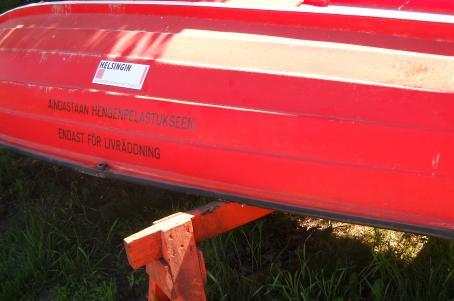 """Punainen ylösalaisin oleva vene, jonka alla nurmikkoa. Veneessä lukee """"Ainoastaan hengenpelastukseen, endast för livräddning""""."""