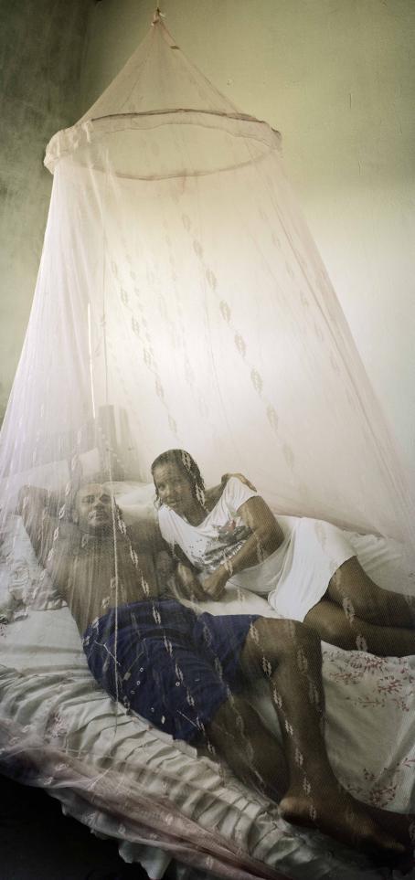 Nainen ja mies makoilevat sängyllä katosta roikkuvan hyttysverkon alla.