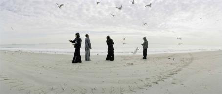 Neljä henkilöä seisoo rannalla ja heidän ympärillään lentää paljon lokkeja.
