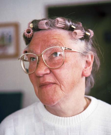 Silmälasipäinen vanha nainen, jolla on papiljotteja hiuksissaan.