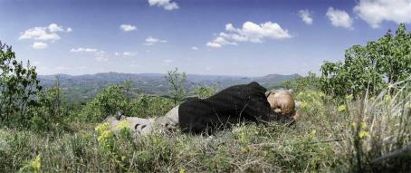 Mies makaa silmät kiinni nurmikolla. Takana näkyy vuoristomaisemaa.