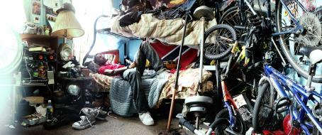 Mies makaa kerrossängyn alemmalla sängyllä. Sängyn vieressä on monta polkupyörää ja huoneessa on paljon tavaraa.
