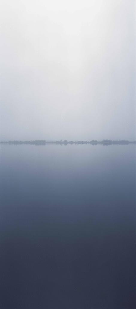 Rauhallinen sinisävyinen kuva, jossa näkyy vettä, horisontissa vähän puita ja taivas.