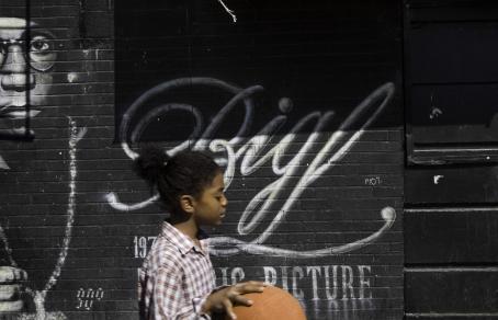 Mustan tiiliseinän edessä kävelee tummaihoinen henkilö, jolla on kädessä koripallo.