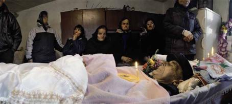 Kuollut mies makaa arkussa ja hänen rinnallaan palaa kynttilä. Arkun takana seisoo ihmisiä rivissä.