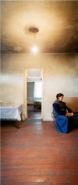 Huone, jonka katosta roikkuu pelkkä lamppu. Nainen istuu tuolilla oviaukon vieressä.