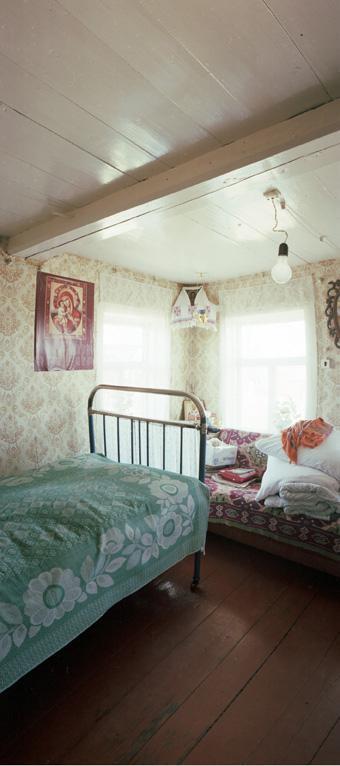 Osa huoneesta, missä on sänky ja sohva sekä kaksi ikkunaa.