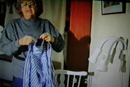 Naisella on käsissään raidallinen paita.