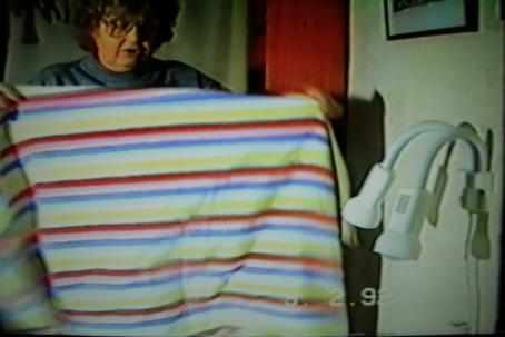 Naisella on käsissään levitettynä raidallinen kangas.