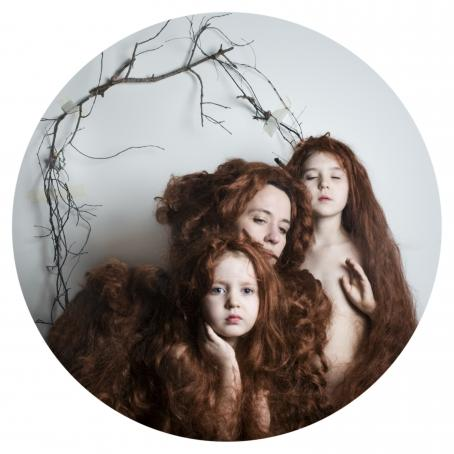 Pyöreässä kuvassa kolme henkilöä, joilla kaikilla on pitkät punaiset hiukset. Hiukset ympäröivät heitä. Takana seinällä on puiden oksia.