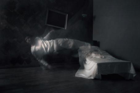 Hämärä huone, jonka reunassa on sänky. Sängyn vieressä on valkoisissa vaatteissa hahmo, joka on ilmassa, vaakasuorassa lattiaan nähden.
