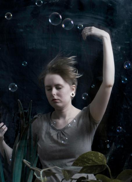 Nainen silmät kiinni, toinen käsi ojennettuna ylöspäin. Naisen hiukset ovat pystyssä, hänen edessään on kasveja ja hänen ympärillään leijuu kuplia.