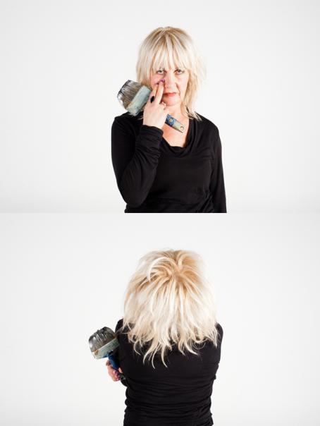 Ylemmässä kuvassa vaaleahiuksinen nainen mustassa paidassa katsoo kohti. Hänellä on kädessään maalipensseli ja hän on painanut kaksi sormea nenän viereen. Alemmassa kuvassa vaaleahiuksinen, mustapaitainen nainen on selin.