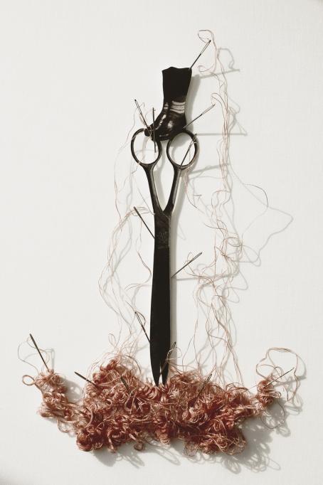 Sakset, joiden päällä on mustat pienet saappaat. Saksien ympärillä törröttää monta neulaa ja niiden alareunassa on kasa lankaa.