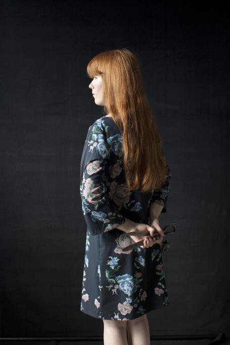 Nainen jolla on kukkakuvioinen mekko ja pitkät oranssit hiukset, pitää selkänsä takana käsissään saksia.