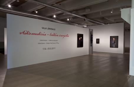 """Näyttelytila. Seinällä lukee """"Ulla Jokisalo, Aikomuksia- leikin varjolla""""."""