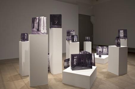 Näyteikkunakuvista tehtyjä paperikasseja näyttelyssä jalustoilla.