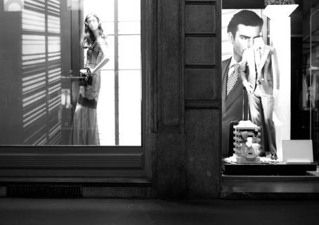 Mustavalkoisessa kuvassa vierekkäin kaksi valaistua näyteikkunaa. Toisessa mallinuken päällä mekko, toisessa puku.