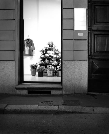 Mustavalkoinen katunäkymä, valaistussa näyteikkunassa näkyy kukka-asetelmia sekä henkarissa roikkuva takki.