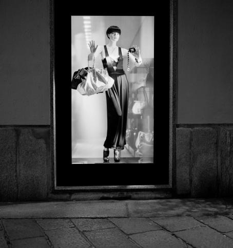 Mustavalkoisessa kuvassa valaistu näyteikkuna, jossa mallinukke kädessään laukkuja.