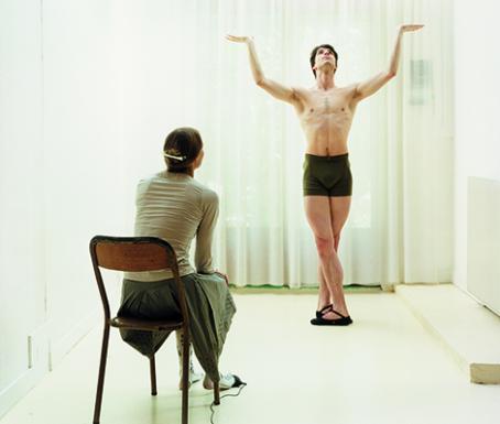Kuvassa on kaksi henkilöä. Toinen istuu tuolilla ja katsoo kun toinen henkilö seisoo ilman paitaa kädet kohotettuina ylöspäin.