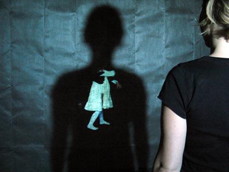 Kuvassa on hahmo, jonka varjo osuu seinään. Varjossa näkyy pieni valkomekkoinen hahmo, jonka ympärillä on musta käsi.