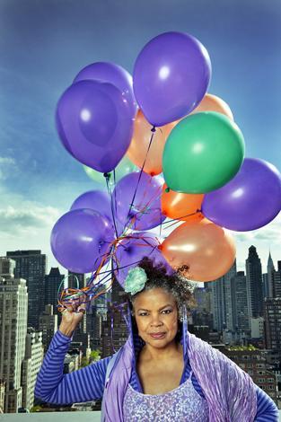 Nainen violeteissa vaatteissa pitää kädessään ilmapalloja. Hänen takanaan näkyy kaupungin korkeita rakennuksia.