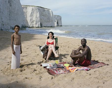 Kolme ihmistä on hiekkarannalla. Tummaihoinen poika seisoo pyyhe lantiolla, valkoihoinen nainen istuu lehti kädessään, tummaihoinen mies istuu pyyhkeen päällä. Heidän takanaan näkyy korkeita valkoisia kallioita.