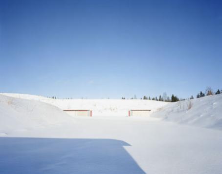 Kumpuileva luminen maisema. Kauempana näkyy maassa näkyy kaksi punareunaista suorakulmiota.