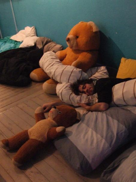 Mies nukkuu lattialla peittoon kääriytyneenä. Hänen vieressään on kaksi isoa nallekarhua.